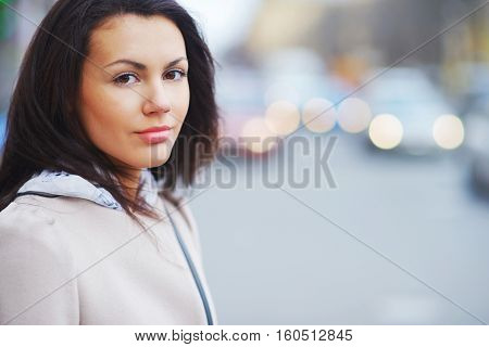 Portrait of a young brown-eyed brunette girl on a beautiful blurred background city street close-up.