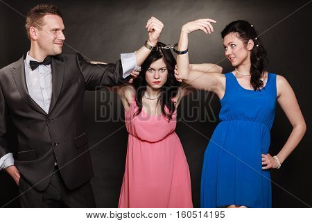 Marital infidelity concept. Love triangle two women one man passion of love hate. Mistress betrayal within the family. Black background.