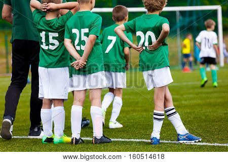 Coaching Youth Sports. Young Boys with Football Coach on Pitch. Youth Soccer Team with Coach and Children Sports Team at the Game