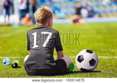 Child in black sportswear with soccer ball. Boy sitting on football pitch. School football match for children