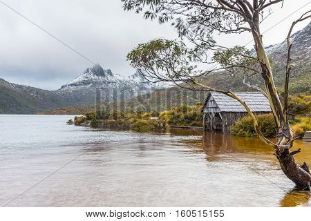 The boat house at Dove Lake in Cradle Mountain NP (Tasmania Australia). In the background, clouds move in around the snow-capped peaks of Cradle Mountain.