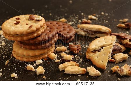 Tasty cookies with crumbs on dark background