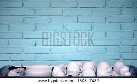 interior background with blue brick wall and white cups in front