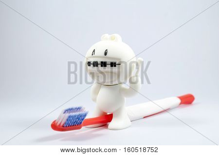A braces doll and a toothbrush on white background.