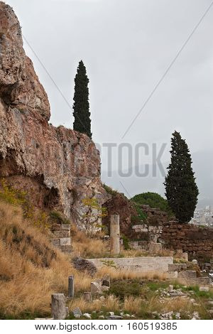 Fir in the middle of the ruined ancient building with columns of marble at the foot of the mountain.