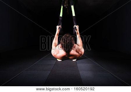 One young handsome brave curly bearded muscled man with a beard makes Total Resistance eXercises fitness trx straps working out in gym crossfit