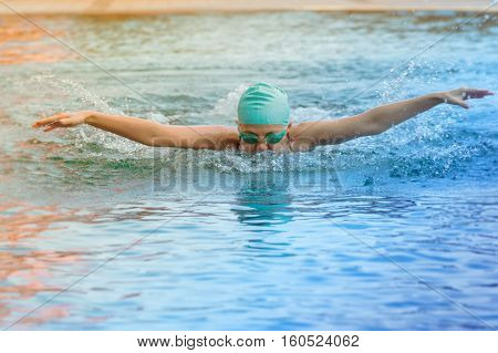 dynamic and swimmer in cap breathing performing the butterfly stroke