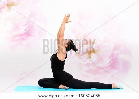 Beautiful Asian woman practicing yoga pose on flower background