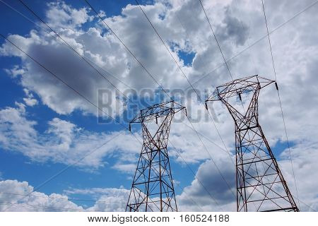 Electricity Power Station At A Sunset.  High-voltage Support. Clouds In The Sky - Scale  Plant Dange