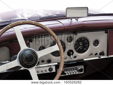 Dashboard of an old classic car with round measuring instruments and wooden steering wheel