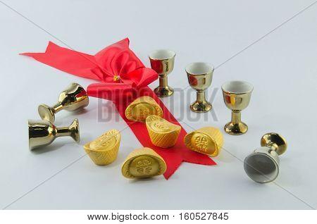 Gold ingot Red ribbon bow Gold jug Tea glass on white background.
