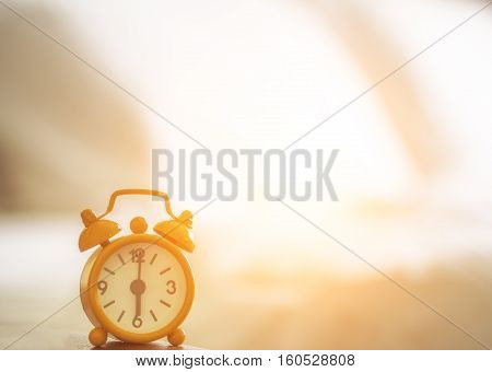 Alarm clock on bed in morning with sun light background bed vintage