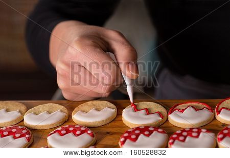 woman decorating homemade cookies, christmas gingerbread decoration