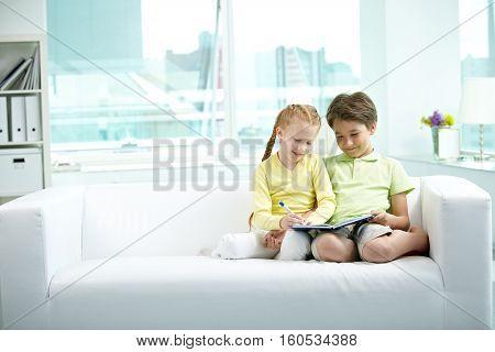 Two little children doing homework together on sofa