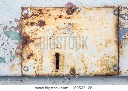 Keyhole on an old metal door with bolts