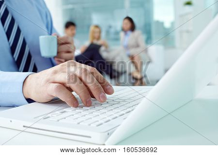 Close-up of a male hand typing on laptop in office