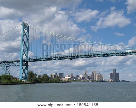On a partly cloudy day the Ambassador Bridge is seen framing the skyline of Detroit Michigan as it crosses the Detroit River to Windsor Ontario Canada.