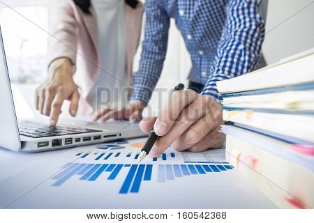 Team work process. young business managers crew working with new startup project. labtop on wood table typing keyboard texting message analyze graph plans