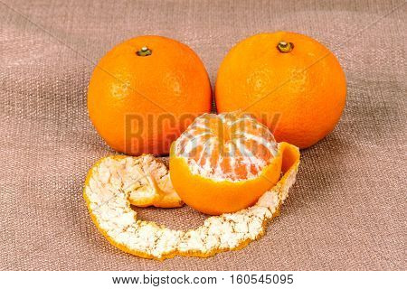 Tangerine on a linen background made of cloth. Fresh ripe fruit diet vitamins.