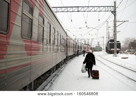 Petrozavodsk, Russia - January 15, 2016: The passenger is on the train station platform winter along the train