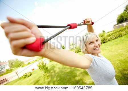Portrait of mature woman practicing with resistance band
