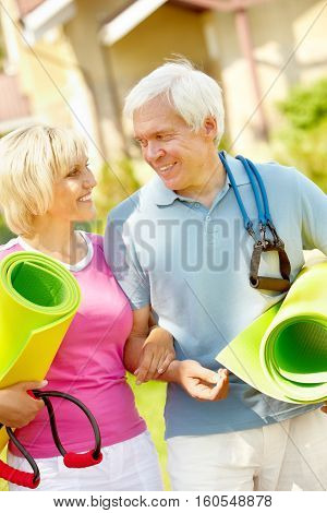Portrait of senior couple with exercise mats and resistance bands
