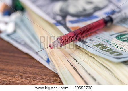 syringe on us Dollar on wooden desk