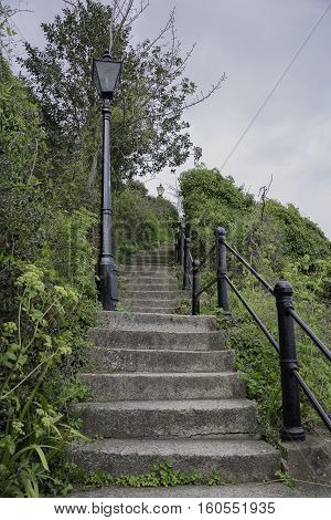 looking up at old remote stone steps with lamp post and metal hand rail