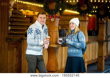 Eve of Christmas. Cute young couple has a good time at the Christmas bazaar. Young people stand near a wooden counter with paper cups in hands. Stall is festively decorated with wreaths and garlands.