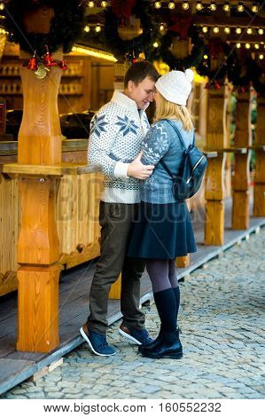 Eve of Christmas. Cute young couple has good time at the Christmas bazaar. Young people stand near wooden counter and gently embrace. Stall is festively decorated with Christmas wreaths and garlands.