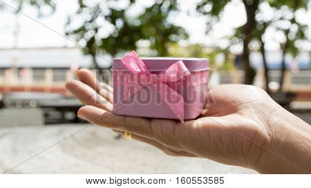 Gift with pink ribbon, white box in female hands, Christmas surprise, a happy new year