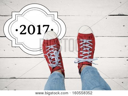 2017 new year wishes with teenager wearing red sneakers against wooden background
