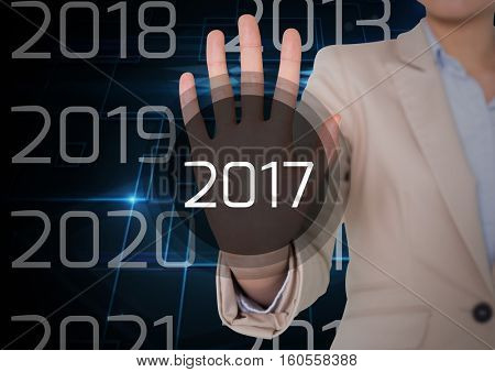 Business woman in digitally generated background touching 2017 new year