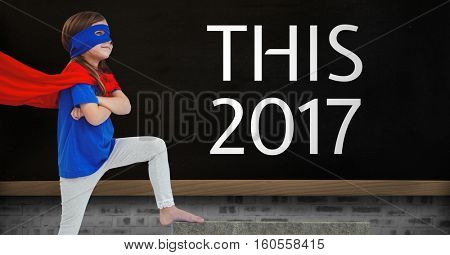 Girl in superhero costume standing near a black board with 2017 new year quotes