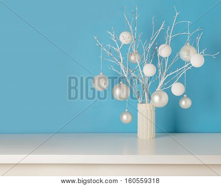 Winter decor. Vase in white knitted cover with white branches and Christmas toys.