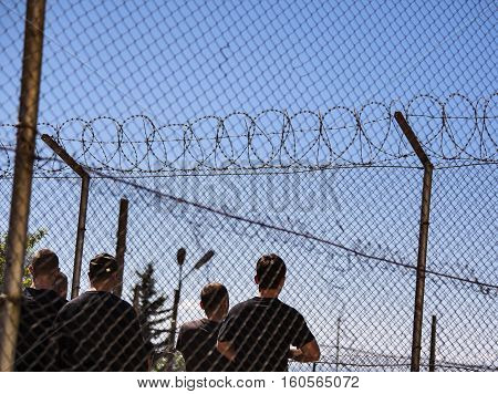 High fence in refugee camp or a jail with razor wire and some people seen from behind.