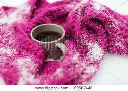 season, drinks, christmas and winter holidays concept - close up of tea or coffee mug and knitted woolen scarf in snow