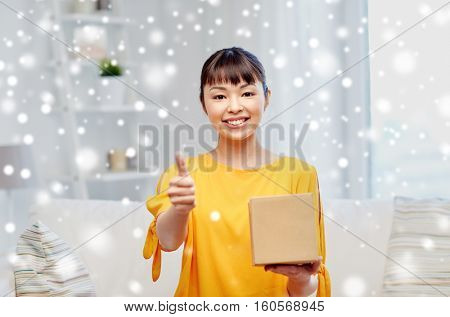 people, delivery, shipping, gesture and shopping concept - happy asian young woman with cardboard parcel box showing thumbs up at home over snow