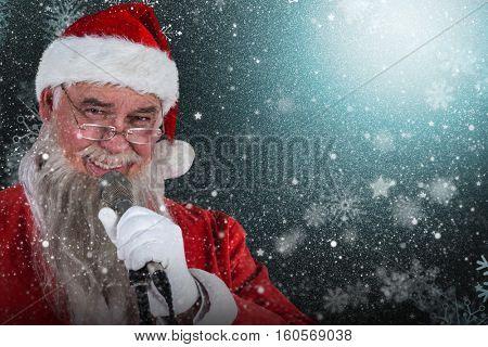 Santa Claus singing Christmas song against snowflake pattern