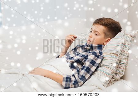 disease, healthcare and medicine concept - ill boy with flu measuring temperature by thermometer at home over snow