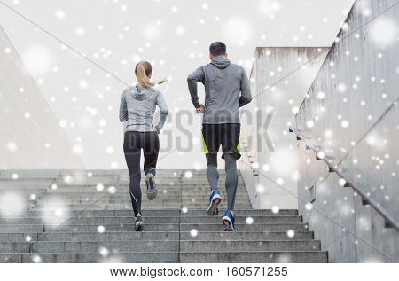 fitness, sport, people, exercising and healthy lifestyle concept - couple of sportsmen running upstairs outdoors over snow