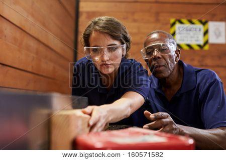 Carpenter Training Female Apprentice To Use Plane