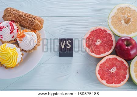 Choosing between Fruits and Sweets. Healthy versus unhealthy food. Weight Loss. Unhealthy tempting cakes and healthy fruits.