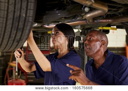 Mechanic And Female Trainee Working Underneath Car Together