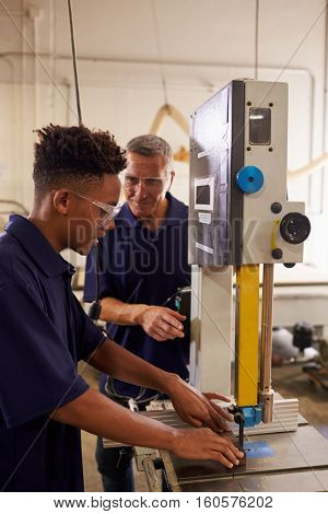 Carpenter Training Male Apprentice To Use Mechanized Saw