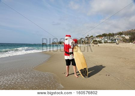 Christmas Santa Claus checks out the waves and surf before going surfing in the ocean.