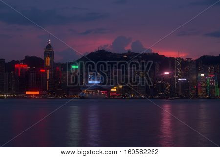 Illuminated Central Plaza, Bank of China Tower on sea shore in business area, mountains at evening in Hong Kong, China