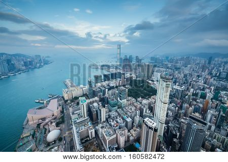 Many skyscrapers in fog on waterside and cloudy sky in Hong Kong, China, view from New World Center
