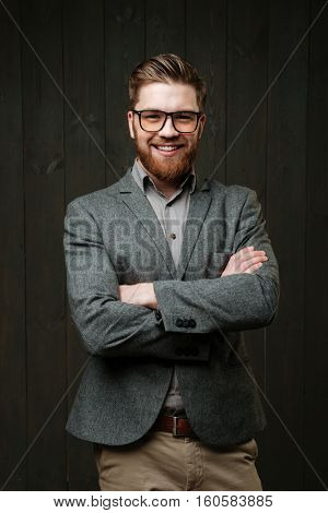 Smiling bearded young businessman standing with arms folded isolated on the black wooden background