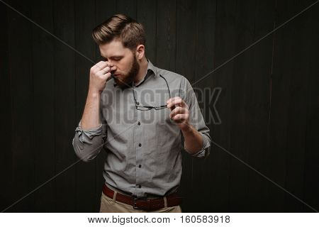Portrait of a tired exhausted bearded man holding glasses and looking away isolated on the black wooden background